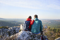 Couple sitting on rock and enjoying the view on a hiking trip in the mountains - BSZF00952