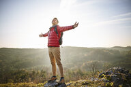 Man on a hiking trip in the mountains standing on rock enjoying the nature - BSZF00958
