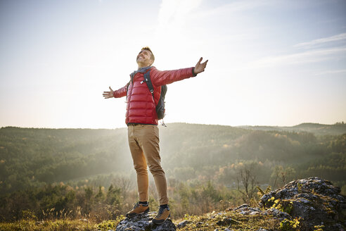 Poland, Polish Jura, Man extending arms in joy while admiring beautiful nature around him - BSZF00958