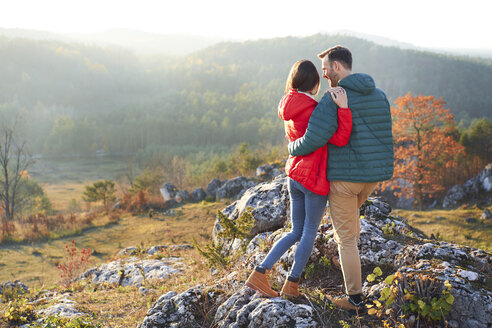 Rear view of couple on a hiking trip in the mountains standing on rock - BSZF00961