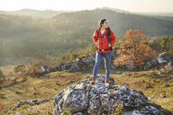 Woman on a hiking trip in the mountains standing on arock - BSZF00964