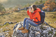 Woman on a hiking trip in the mountains sitting on rock looking through binoculars - BSZF00967