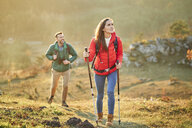Couple walking on alpine meadow on a hiking trip in the mountains - BSZF00979