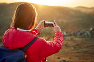 Woman on a hiking trip taking smartphone photo at sunset - BSZF00985