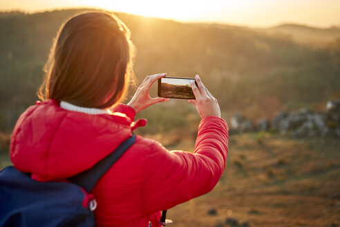 Poland, Polish Jura, Woman taking photo of beautiful sunset during hiking trip in the hills - BSZF00985