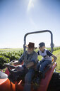 Grandfather farmer and grandson driving tractor on sunny farm - HEROF20900