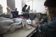 Female fashion design student using sewing machine in studio - HEROF20954