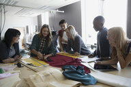 Instructor watching fashion design students cutting fabric at workbench in studio - HEROF20960