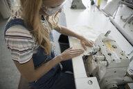 Female fashion design student using serger in studio - HEROF20966