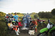Male friends drinking beers around campfire near motorbikes in rural field - HEROF20993