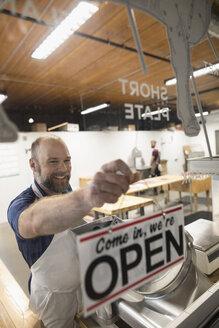 Male butcher changing open sign in butcher shop window - HEROF21020