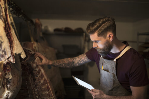 Male butcher with digital tablet examining meat slabs dry aging - HEROF21023