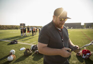 High school football coach reviewing game plan on clipboard on sunny football field - HEROF21026