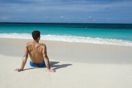 Caribbean, Anguilla, man sitting on the beach, rear view - RUNF01170