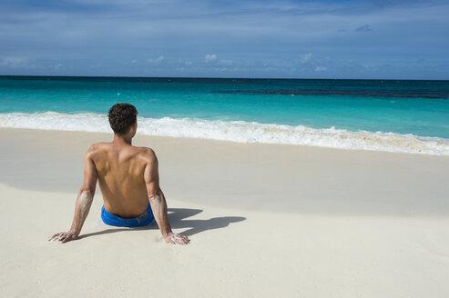 Caribbean, Anguilla, man sitting on the beach, rear view - RUNF01170