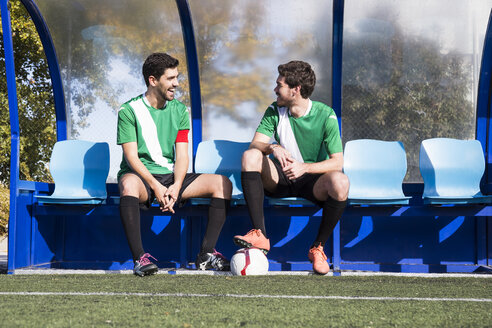 Football players sitting on bench and having nice chat before match. - ABZF02177