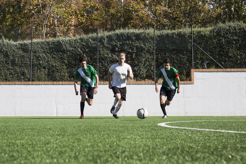 Group of players in sportswear kicking ball around soccer field playing in teams. - ABZF02186