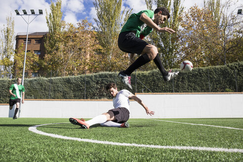 Determined player kicking ball around field overjumping player on ground. - ABZF02189