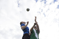 Football players jumping to head the ball during a football match - ABZF02192