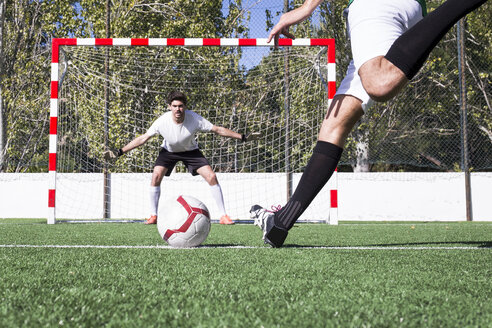 Fast football player in motion of kicking ball with strength during game on field. - ABZF02207