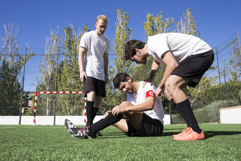 Soccer players helping a injured player during a soccer match. - ABZF02213