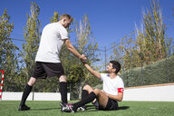 Football player helping an injured player during a match - ABZF02216