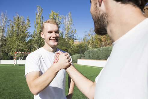 Two football players shaking hands on football field - ABZF02222