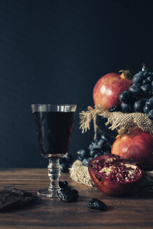 Fruits and glass of vine on dark wood - MOMF00625