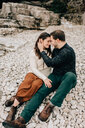 Couple sitting on rocky ground, Tobermory, Canada - ISF20639