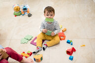 Baby boy and brother playing with toys on floor - ISF20684