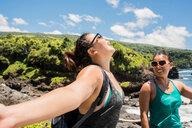 Hikers enjoying sunshine on coast of Waipipi Trail, Maui, Hawaii - ISF20753