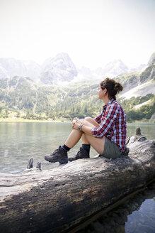 Austria, Tyrol, woman sitting on tree trunk at lake Seebensee - FKF03264