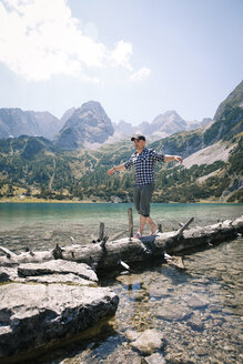 Austria, Tyrol, man balancing on tree trunk at lake Seebensee - FKF03273