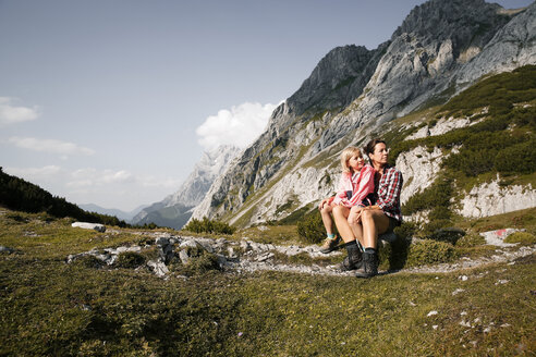 Austria, Tyrol, mother with daughter resting in mountainscape - FKF03279