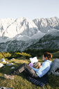 Austria, Tyrol, mother and daughter reading book in mountainscape - FKF03285