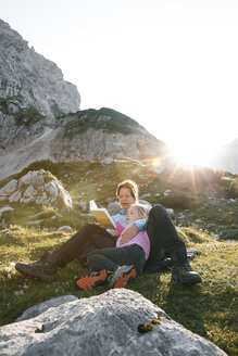 Austria, Tyrol, mother and daughter reading book in mountainscape at sunset - FKF03288