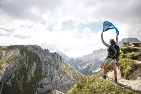 Austria, Tyrol, woman on a hiking trip in the mountains holding cloth - FKF03294
