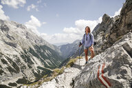 Austria, Tyrol, happy woman on a hiking trip in the mountains - FKF03306