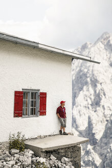 Austria, Tyrol, man on a hiking trip standing at mountain hut - FKF03309