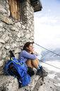 Austria, Tyrol, woman on a hiking trip resting at mountain hut - FKF03318