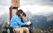 Austria, Tyrol, mother and son on a hiking trip with book at the summit - FKF03327