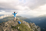 Austria, Tyrol, woman on a hiking trip in the mountains cheering on peak - FKF03333