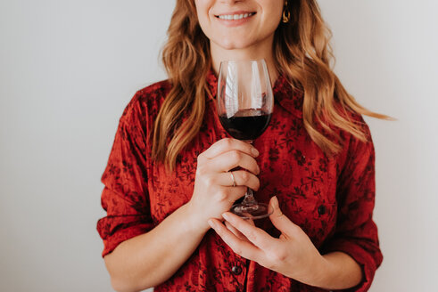 Woman holding glass of wine, white background - ISF20787