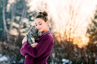 Girl hugging french bulldog puppy outdoors - ISF20790