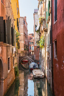 Narrow canal with moored boats, old architectural style stucco and brick residential buildings, San Marco, Venice, Veneto, Italy - ISF20808