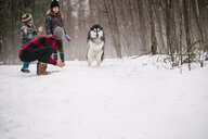 Family with pet dog playing in snow landscape - ISF20835