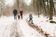 Family with pet dog on walk in snow landscape - ISF20838