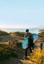 Young man with surfboard on beach, Morro Bay, California, United States - ISF20841