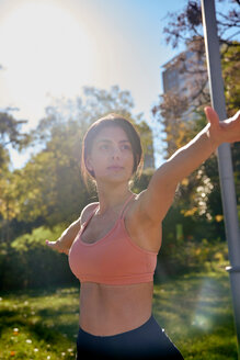 Woman practising yoga in city park, Barcelona, Catalonia, Spain - ISF20868