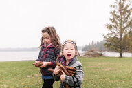 Siblings with armful of brown pine cones, Kingston, Ontario, Canada - ISF20880